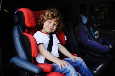 baby boy sitting in a red child car seat