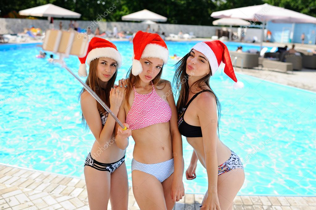 Three girls in bathing suits and caps of Santa Claus on the selfie shoot pool background