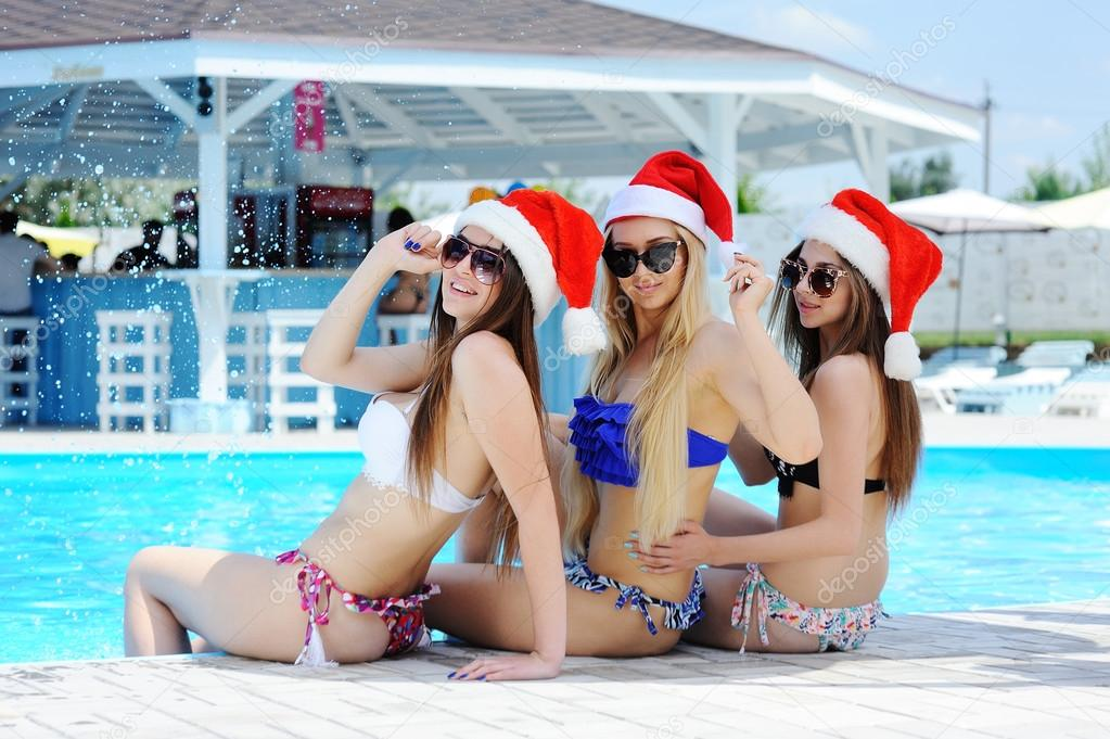 Three girls in bathing suits and caps of Santa Claus on a pool background