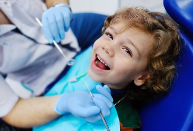 child with curly hair at the dentist