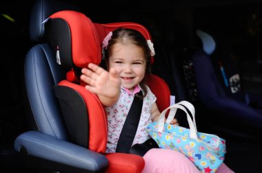 aby girl sitting in a child car seat