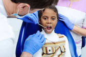 Photo little African girl with dark skin in dentistry