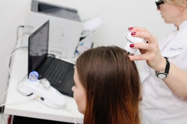 dermatologist examines a patient woman hair using a special device