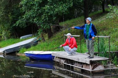 Two fishermen catch fish standing on the bridge