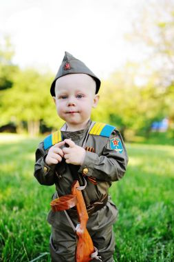 Child in military uniform against nature background
