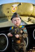 Kind in Militäruniform auf dem Panzerhintergrund