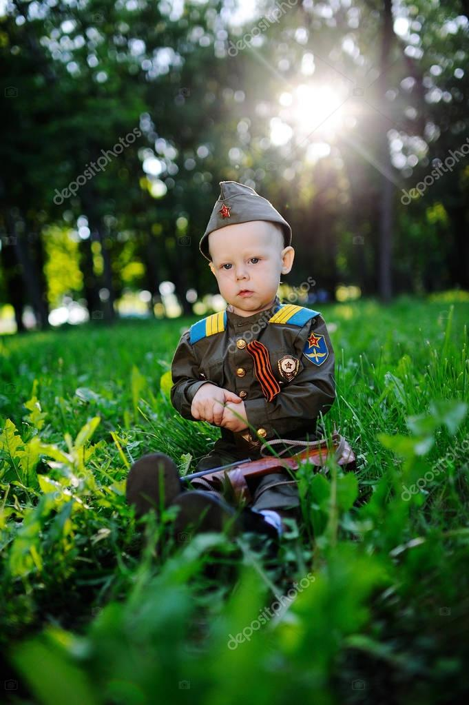 A child in military uniform sits in the grass