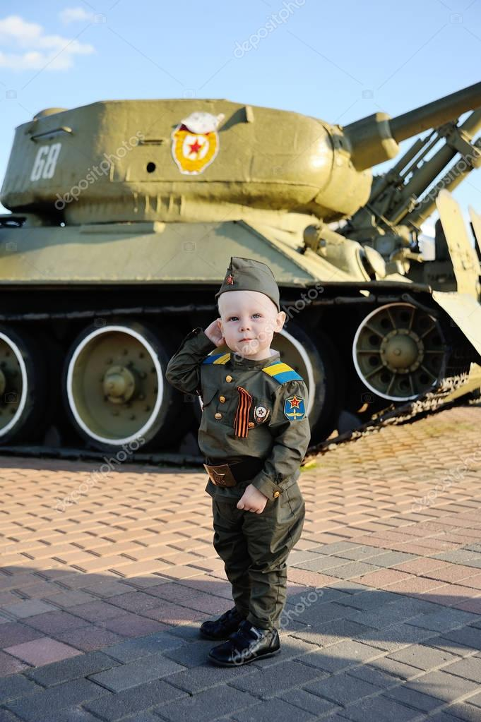 Child in military uniform on the tank background