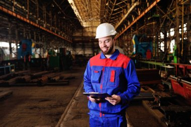 Worker in a helmet with a tablet