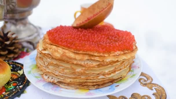 Pfannkuchen mit rotem Kaviar close-up auf dem Hintergrund der festlich gedeckten Tisch. Karneval in Russland