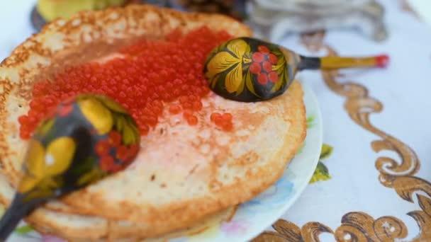Pfannkuchen mit rotem Kaviar in Großaufnahme auf dem Hintergrund der festlichen Tafel. Karneval in Russland