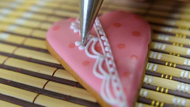 žena cukrář zdobí a zdobí poleva s perníčky ve tvaru srdce