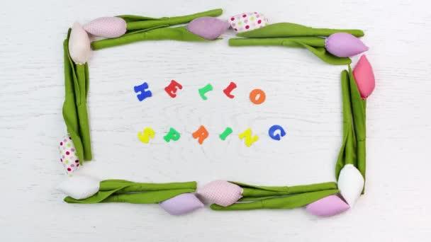 nápis z pestrobarevným písmen Ahoj jaro uvnitř rámečku hračka tulipánu květin