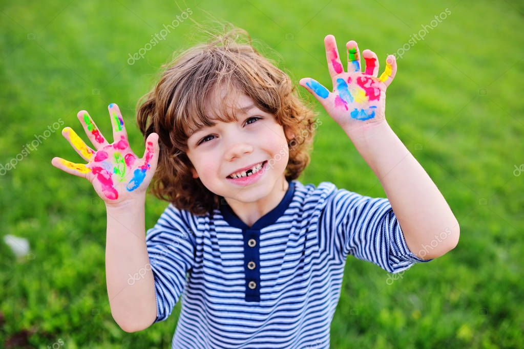 boy with curly hair without front milk tooth shows hands dirty with multi-colored finger paints and smiles.