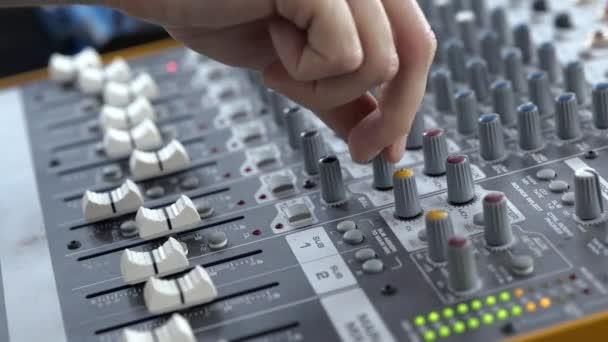 Mladý muž v nahrávacím studiu. Zblízka video mužských rukou otáčení a nastavení elektroniky a ekvalizéru.