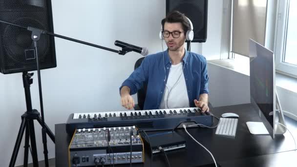 Mladý muž v nahrávacím studiu. Guy pozdravuje a začne pracovat s nastavením zvukové konzole. Profesionální hudební vybavení.