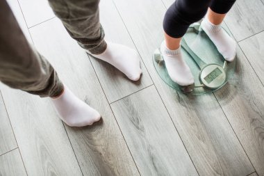 Father and daughter are weighed on indoor household scales. Funny and joyful moments having fun in the family.