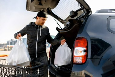buying food in a supermarket. Shopping A young man buys food for a week in a large shopping center in the countryside. Folds bags of vegetables, fruits, meat and dairy products in a car park