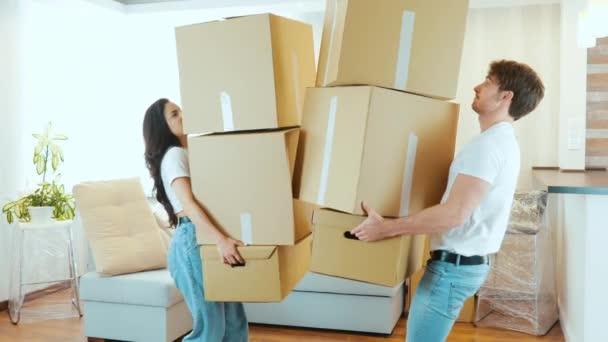 Junges Paar bezieht neue Wohnung Zeitlupe von Menschen kollidierten. Kisten fallen ihnen aus den Händen. Verärgerter Kerl geht weißes Mädchenlächeln ein wenig weg. Umverteilungsprozess.