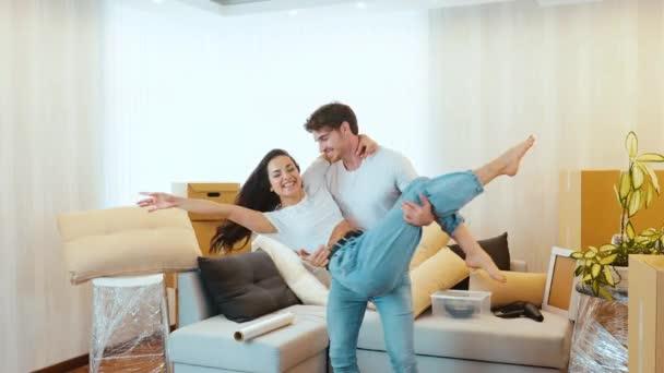Junges Paar bezieht neue Wohnung Zeitlupe des Mannes hält die Frau an den Händen und dreht sie herum. Paar zusammen in ihrer neuen Wohnung. Zeit miteinander verbringen.