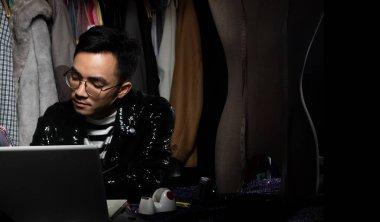 Asya Moda Tasarımcısı 'nın Kara Sequin ceketi Not Defteri bilgisayarındaki siparişleri ve satışları kontrol ediyor. Gey terzi kumaş raf arkaplanları için yeni koleksiyon trendi tasarladı, düşük tuş pozlama kopya alanı