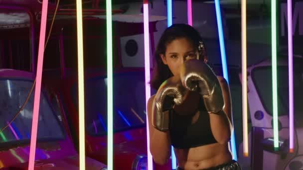 Athletin Asian Transgender trainiert und boxt mit silbernen Handschuhen. Schöne Office Girl Übungen in moderner Farbe Neon Muay Thai Tuk Tuk Box Gym, statisches Medium Shot 4k Zeitlupe