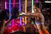 Photo Beautiful 20s Asian Woman trains punching with coach on Silver fashion Mitts Gloves. Office Girl exercise at Modern multi color Neon Muay Thai Boxing Gym background with sweat water splash light
