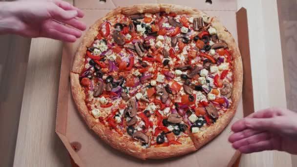 Pohled shora na lidské ruce, které berou pizzu s plátky z krabice
