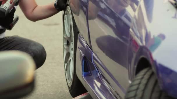 Opravář používá přenosný pneumatický nástroj, šroubovák pro upevnění hliníkového disku