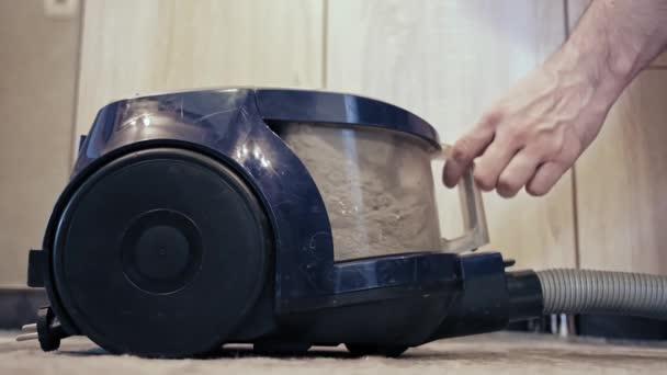 Ein Mann hebt vom Staubsauger einen gefüllten wiederverwendbaren Staubbeutel und einen Staubfilter ab