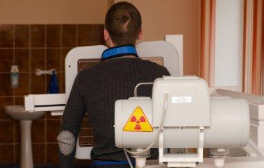Young man undergoes annual mandatory fluorographic examination on digital X-ray apparatus