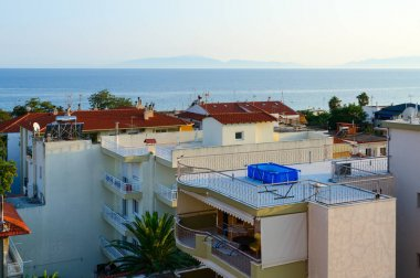 Top view of traditional Greek low-rise buildings on background of sea, Nea Kallikratia, Halkidiki peninsula, Greece