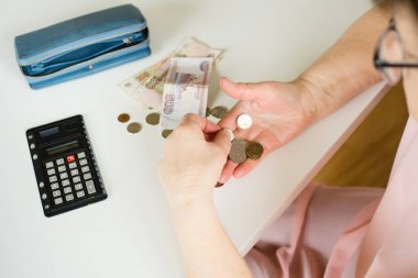 close-up of an elderly woman's hand counting coins Russian rubles on the background of a first-aid kit with medicines on a white table background place for text
