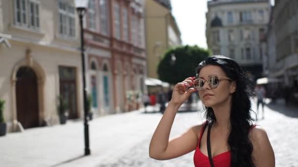 Mladá brunetka se slunečními brýlemi stojí na ulici, rozhlíží se a užívá si volného času v historické části Bratislavy v SLOW MOTION HD VIDEO. Poloviční rychlost, přední pohled.