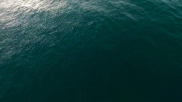 Vzduch Nad klidným oceánem Povrch vody s modrými vlnami a vlnami pomalý pohyb s paprskem slunečního světla odraz sluneční paprsky