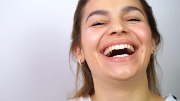 Vonzó, vegyes bőrű nő nevetett és a kamerába nézett. Gyönyörű fogak, szemek és ajkak. Szekrény portré fehér háttér.