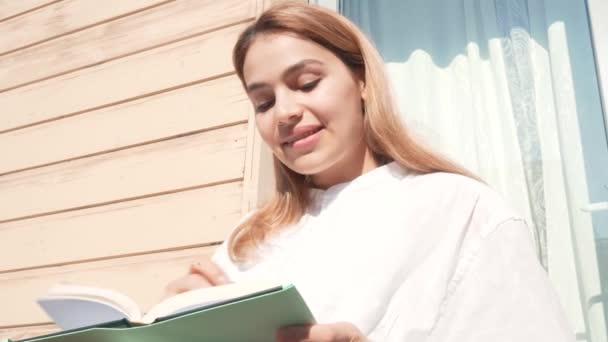Glückliche schöne Studentin, die von zu Hause aus studiert. Attraktive Geschäftsfrau schreibt an einem sonnigen Tag in ihr Notizbuch.