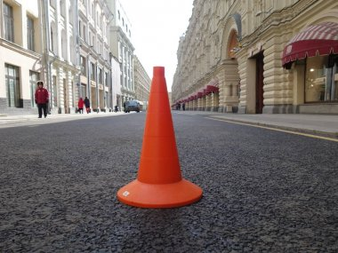 orange traffic cone on the background of black crushed-mastic asphalt