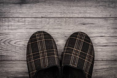 Slippers on wooden background.