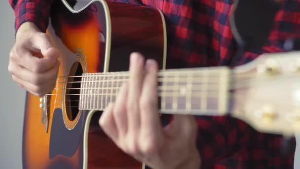 music, creativity, concert, self-isolation concept. Close-up hands of young man playing an acoustic guitar dreadnought in soft focus. Fingers sort out strings by pressing chords on frets of fretboard.