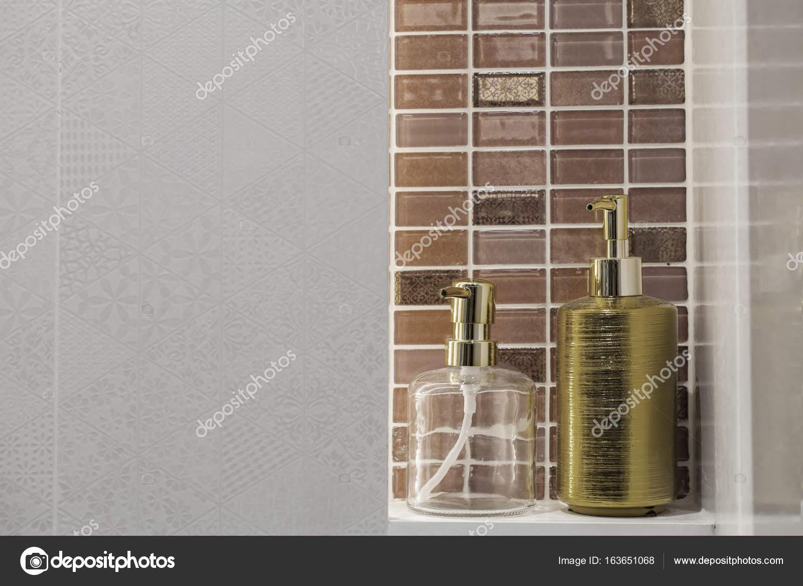 Bottiglia di sapone liquido chiaro e dorato con priorità