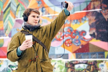 Man listening to music on headphones, photographs and drinking coffee in the winter on the street. Concept of technology and lifestyle