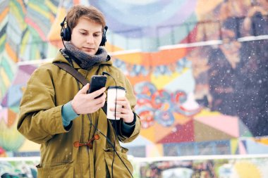 Man listening to music on headphones and drinking coffee in the winter on the street. Concept of technology and lifestyle