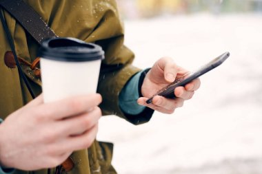 Man holding a cup of coffee in their hands and looking at phone on the street in winter