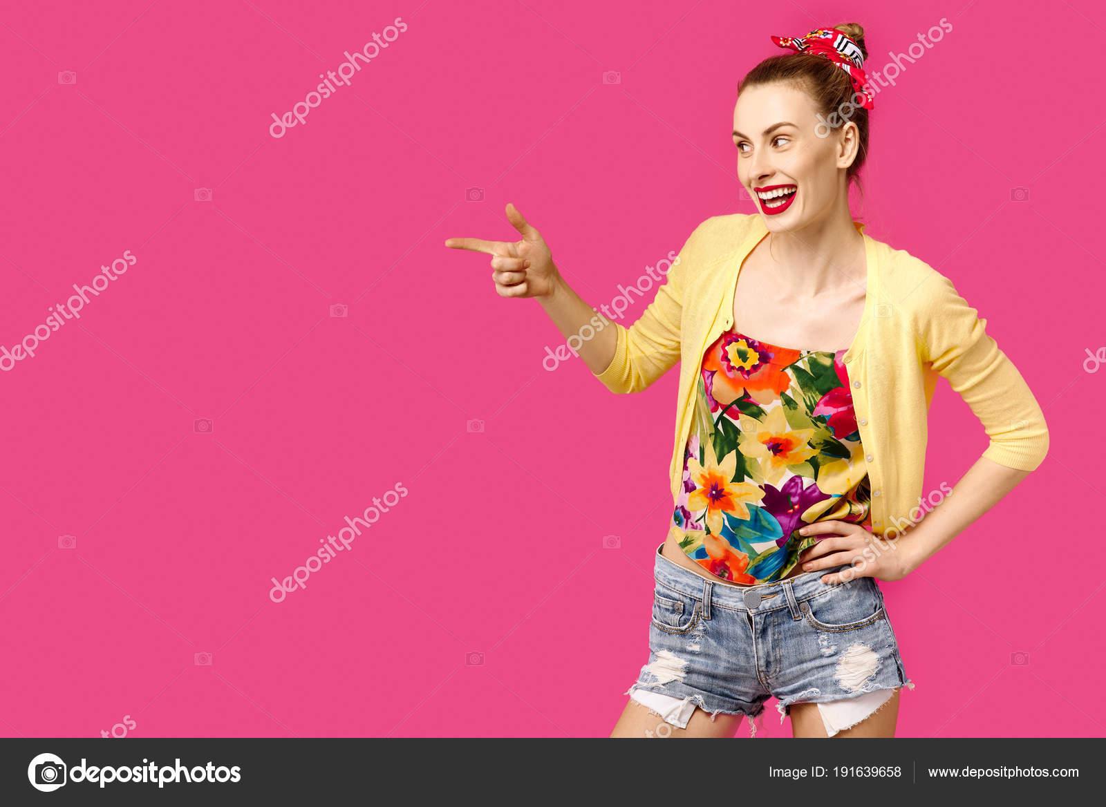 72a4da8470d Krásná mladá dívka v žlutém svetru na růžovém pozadí zobrazuje ok. Barevný  koncept posedlost. Minimalistický styl