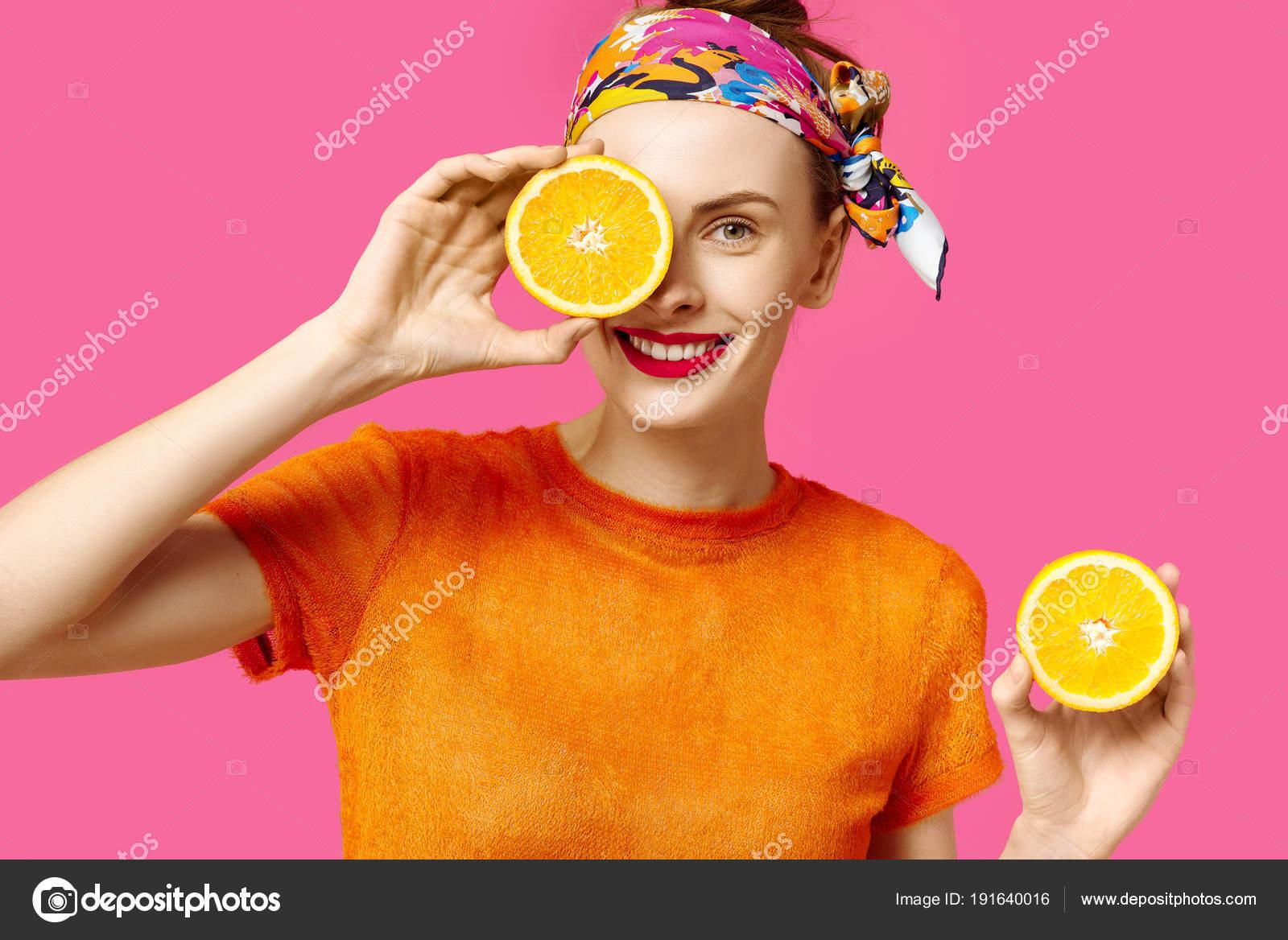 59c0a5bdf16 Mladá žena na růžovém pozadí drží řez oranžové v ruce a smích. Barevný  koncept posedlost. Minimalistický styl. Stylové Trendy — Fotografie od ...