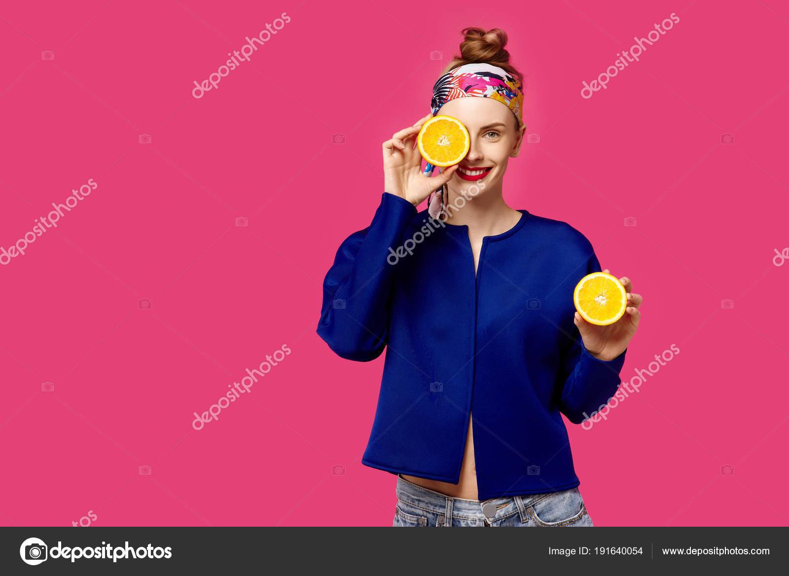 9039caa884b Mladá žena na růžovém pozadí drží řez oranžové v ruce a smích. Barevný  koncept posedlost. Minimalistický styl. Stylové Trendy — Fotografie od  khmelev