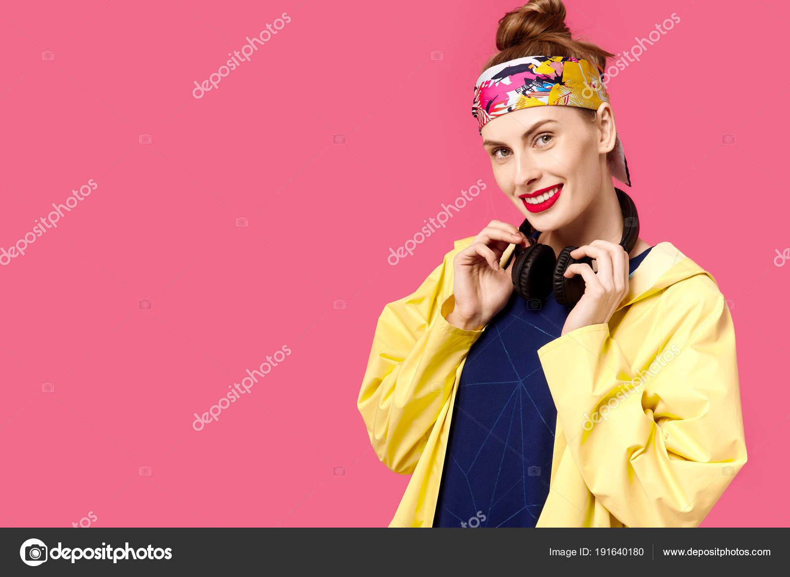 359a125d34a ... žena na růžovém pozadí a žlutý kabát posloucháte hudbu prostřednictvím  bezdrátových sluchátek. Pojem zdravé výživy a sportu. Barevný koncept  posedlost.