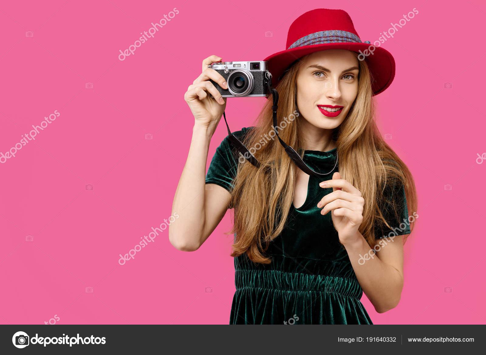 5642e87b160 Mladá krásná žena na růžovém pozadí v zelené šaty a klobouk drží rarita  kameru v ruce a úsměvem. Pojem zdravé výživy a sportu. Barevný koncept  posedlost.