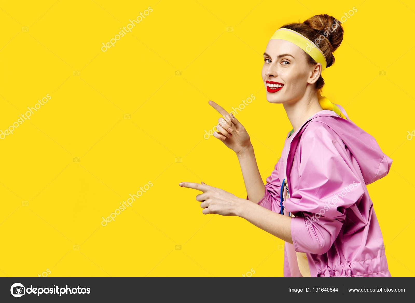35872775f16 Mladá žena na žlutém pozadí a růžový kabát. Barevný koncept posedlost.  Minimalistický styl. Stylové Trendy– stock obrázky